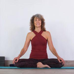 Woman sitting in yoga pose smiling