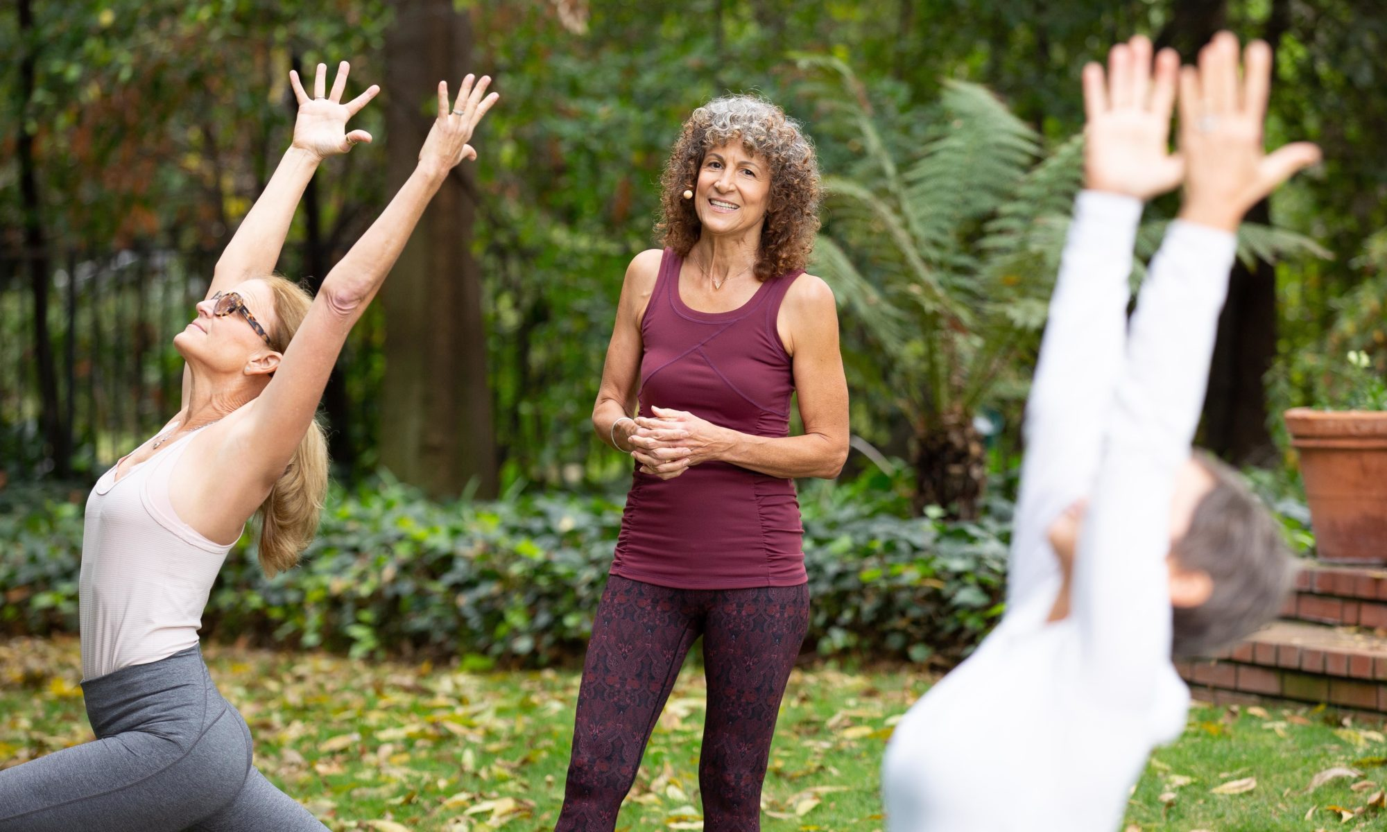 Desiree standing among yoga students outdoor in a lush garden area