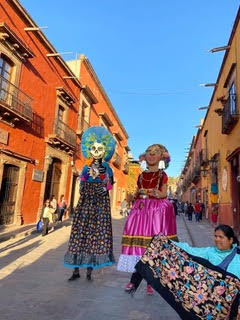 two people dressed up in parade down Mexico street